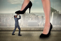 Composite image of businesswoman stepping on tiny businessman Stock Photo