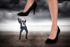 Composite image of businesswoman stepping on tiny businessman Royalty Free Stock Photo