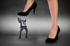 Composite image of businesswoman stepping on tiny businessman Stock Images