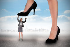 Composite image of businesswoman stepping on tiny businesswoman Stock Photography