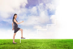 Composite image of businesswoman stepping up. Businesswoman stepping up against blue sky over green field Royalty Free Stock Photo