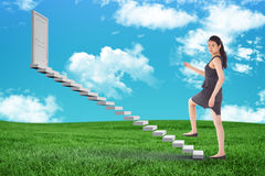 Composite image of businesswoman stepping up. Businesswoman stepping up against green field under blue sky Stock Photography