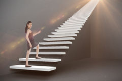 Composite image of businesswoman stepping up 3d. Businesswoman stepping up against grey 3d Royalty Free Stock Image