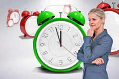 Composite image of businesswoman thinking with hand on chin Stock Images