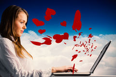 Composite image of businesswoman typing on her laptop Royalty Free Stock Photos
