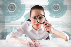 Composite image of businesswoman typing and looking through magnifying glass Royalty Free Stock Photo