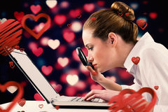 Composite image of businesswoman typing and looking through magnifying glass Stock Images