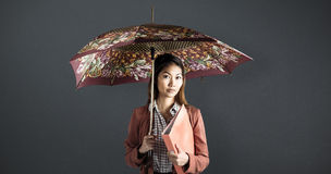 Composite image of businesswoman with an umbrella holding a binder. Businesswoman with an umbrella holding a binder against grey background Royalty Free Stock Images