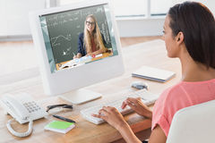 Composite image of businesswoman using computer at desk in creative office Royalty Free Stock Images
