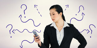 Composite image of businesswoman using mobile phone Royalty Free Stock Image