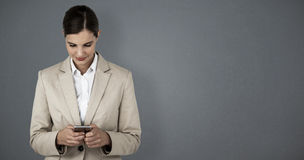 Composite image of businesswoman using mobile phone Royalty Free Stock Images