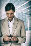 Composite image of businesswoman using mobile phone Stock Photos
