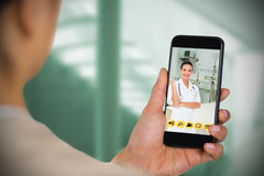 Composite image of businesswoman using mobile phone. Businesswoman using mobile phone against sterile bedroom Stock Photo