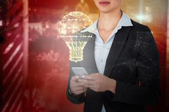 Composite image of businesswoman using mobile phone over white background Royalty Free Stock Photography