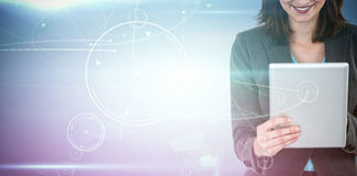 Composite image of businesswoman using tablet. Businesswoman using tablet against circles on glowing background Stock Photo
