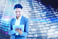 Composite image of businesswoman using a tablet with colleagues behind Royalty Free Stock Image