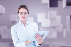 Composite image of businesswoman using tablet pc Stock Photography