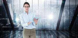 Composite image of businesswoman using tablet pc Stock Images