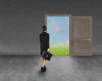 Composite image of businesswoman walking away. Composite image of businesswoman standing back to camera in room with keyhole shaped door Royalty Free Stock Image