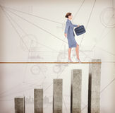 Composite image of businesswoman walking tightrope Royalty Free Stock Images