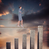 Composite image of businesswoman walking tightrope Stock Image