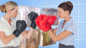 Composite image of businesswomen with boxing gloves fighting Royalty Free Stock Photo