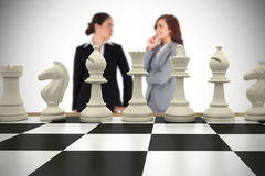 Composite image of businesswomen and chess pieces Stock Photography
