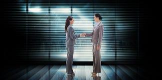 Composite image of businesswomen shaking hands Stock Photo