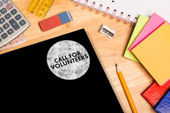 Composite image of call for volunteers. Call for volunteers against students desk Royalty Free Stock Photo