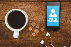 Composite image of call for volunteers. Call for volunteers against view of a black smartphone with a cup of coffee Royalty Free Stock Photo