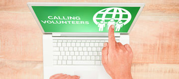 Composite image of calling volunteers text with icons on green screen. Calling Volunteers text with icons on green screen against hand pointing on blank laptop Royalty Free Stock Images
