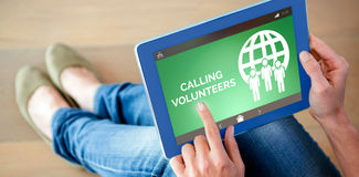 Composite image of calling volunteers text with icons on green screen. Calling Volunteers text with icons on green screen against low section of woman using Royalty Free Stock Image