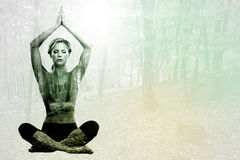 Composite image of calm blonde meditating in lotus pose with arms raised. Calm blonde meditating in lotus pose with arms raised against autumnal forest Stock Images