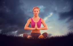 Composite image of calm blonde sitting in lotus pose with hands together Stock Photo