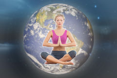 Composite image of calm blonde sitting in lotus pose with hands together. Calm blonde sitting in lotus pose with hands together against stars twinkling in night Royalty Free Stock Image