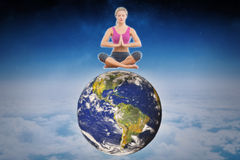Composite image of calm blonde sitting in lotus pose with hands together Stock Image
