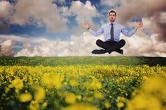 Composite image of calm businessman sitting in lotus pose Stock Photos