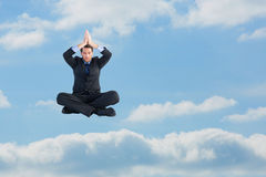 Composite image of calm businessman sitting in lotus pose with hands together Royalty Free Stock Photo