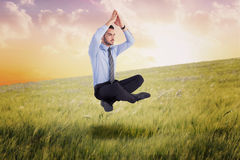 Composite image of calm businessman sitting in lotus pose with hands together Stock Image