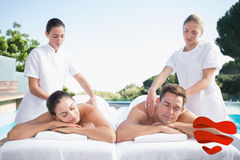 Composite image of calm couple enjoying couples massage poolside Royalty Free Stock Image