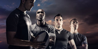 Composite image of calm rugby player thinking while holding ball Stock Image