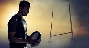 Composite image of calm rugby player thinking while holding ball. Calm rugby player thinking while holding ball against goals posts Stock Photos