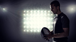 Composite image of calm rugby player thinking while holding ball Royalty Free Stock Images