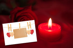 Composite image of candle with red rose. Candle with red rose against white card Stock Photo