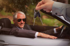 Composite image of car dealer giving keys to a customer. Car dealer giving keys to a customer against smiling mature businessman driving classy car Stock Photography
