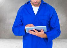 Composite image of car mechanic using digital tablet. Against grey background Stock Image