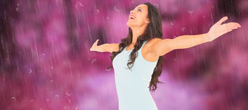 Composite image of carefree brunette with arms out Royalty Free Stock Photo