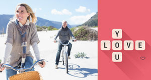 Composite image of carefree couple going on a bike ride on the beach. Carefree couple going on a bike ride on the beach against love you tiles Stock Photo