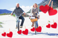 Composite image of carefree couple going for a bike ride and picnic on the beach. Carefree couple going for a bike ride and picnic on the beach  against hearts Royalty Free Stock Photography