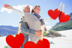 Composite image of carefree couple hugging on the beach in warm clothing. Carefree couple hugging on the beach in warm clothing against hearts hanging on a line Stock Photography